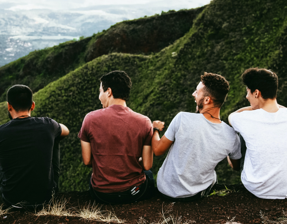 Four laughing men sitting on a mountain trail over looking a green valley